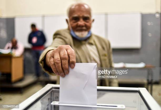 Man casts his vote just before polls close at a polling station in Algeria's capital Algiers on November 1 during a referendum on a revised...