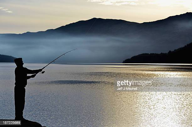 A man casts off his fishing rod from Inversnaid Pier on November 30 2012 in Loch Lomond Scotland Weather warnings have been issued as temperatures...