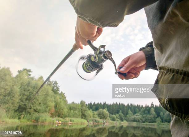 a man catches a fish with a rod in his hands. - pike fish stock pictures, royalty-free photos & images