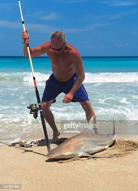 man catches black tip reef shark