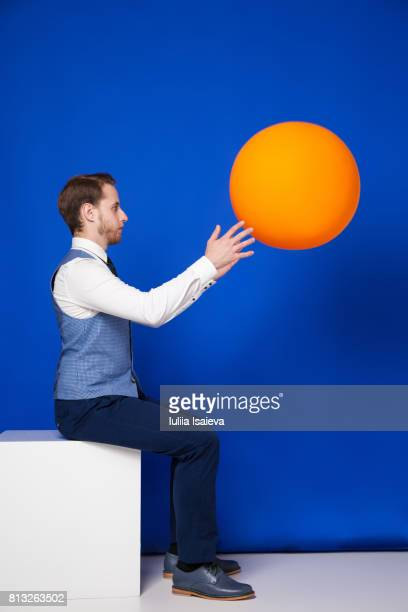 man catching ball on blue - multi colored suit stock photos and pictures