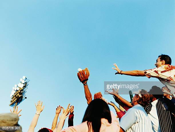 Man catching baseball with mitt, hands reaching for ball