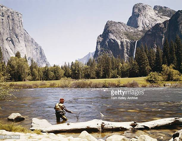 man catching fish at riverside with mountains in background - 1950 1959 stock pictures, royalty-free photos & images