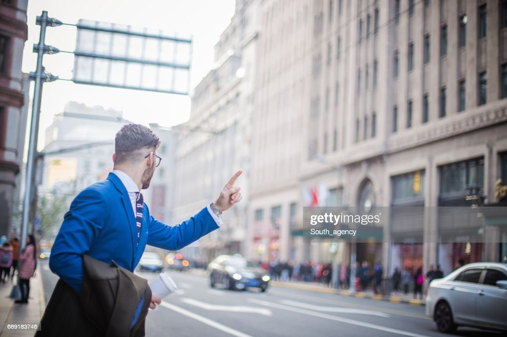 Man catching taxi in city : Stock Photo