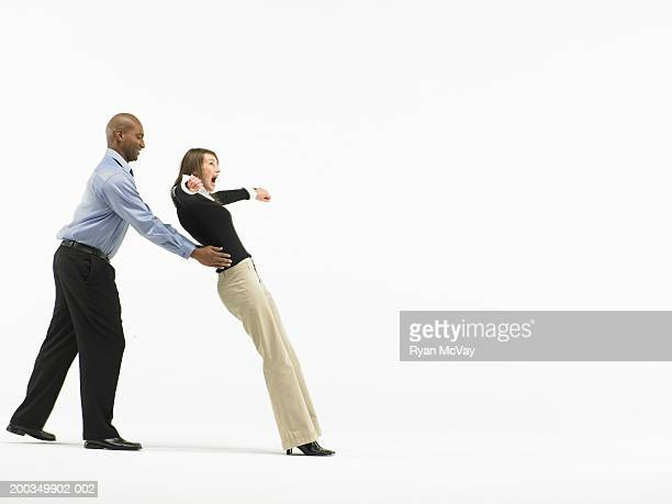 man catching woman falling back by waist, side view - trust stock pictures, royalty-free photos & images
