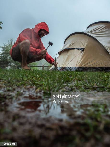 man caught in a rainstorm while camping - mid adult stock pictures, royalty-free photos & images