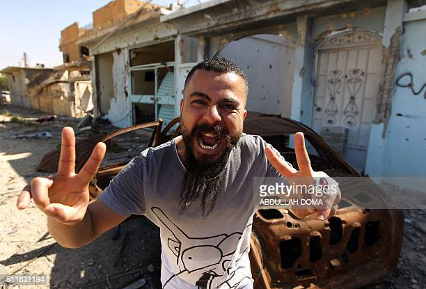 TOPSHOT A man celebrates in the streets of Benghazi as fighters loyal to Libya's internationally recognised government come close to seizing the...