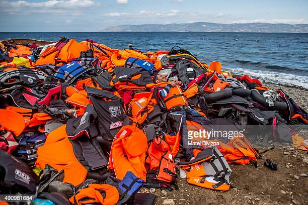 A man celebrates on a mound of life jackets as he arrived with other refugees on the shores of the Greek island of Lesbos after crossing the Aegean...