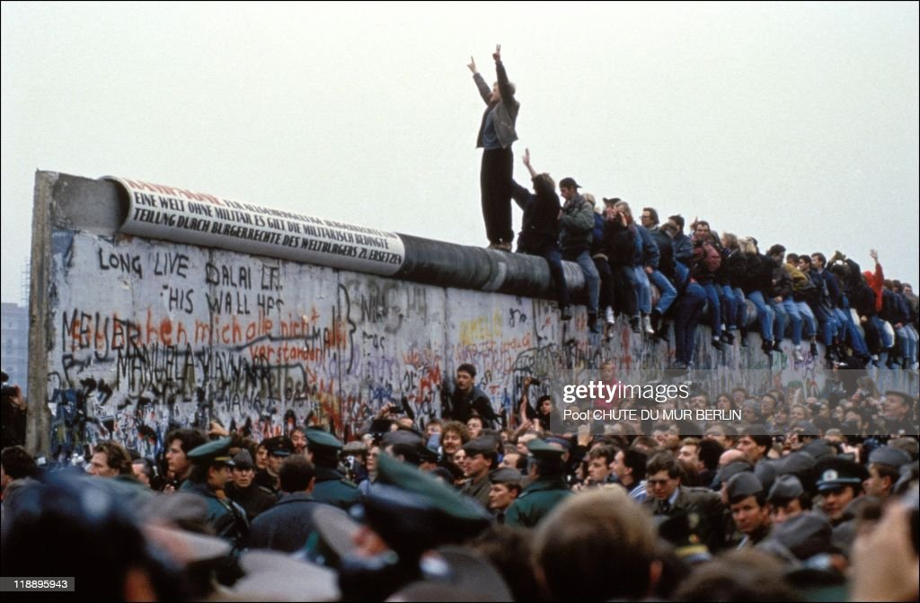A man celebrates on the Berlin wall on November 12, 1989 in Berlin, Germany.
