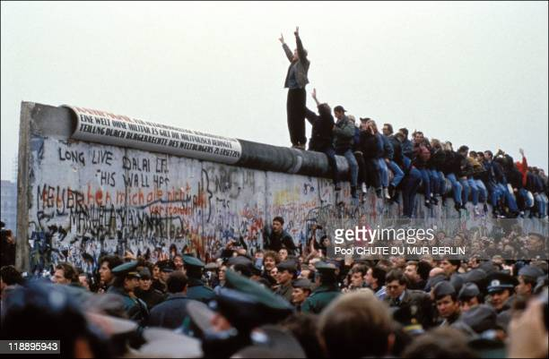 Man celebrates on the Berlin wall on November 12, 1989 in Berlin, Germany.