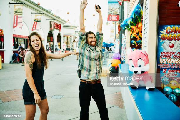 man celebrating after winning carnival game at amusement park - incidental people stock pictures, royalty-free photos & images