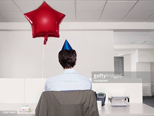 Man celebrating birthday, working alone in office