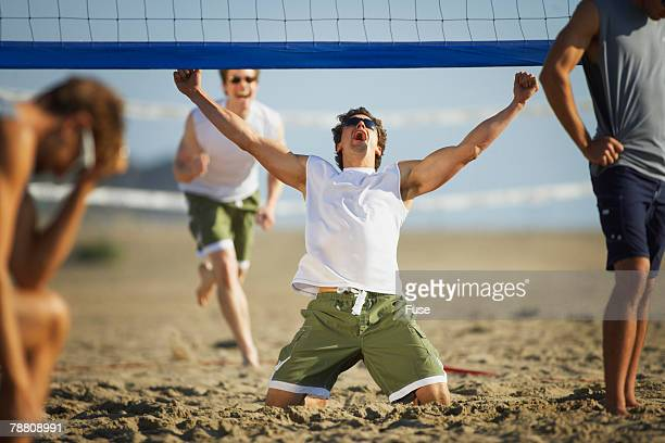 man celebrating during beach volleyball game - strand volleyball der männer stock-fotos und bilder