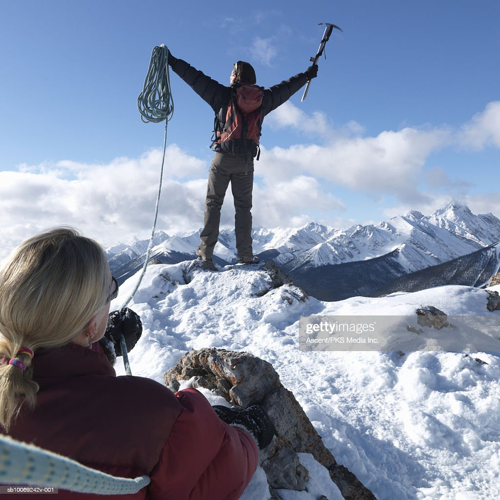 Man celebrating on mountain peak holding climbing equipments, woman in background, rear view : Stockfoto