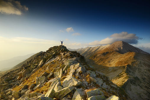 Man celebrating on top of a peak - gettyimageskorea
