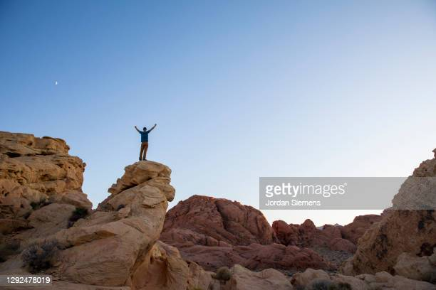 a man celebrating on top of a rocky point with the moon in the distance. - las vegas stock pictures, royalty-free photos & images