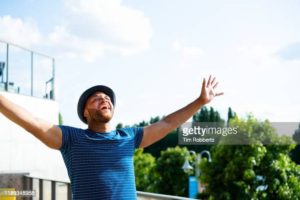 man celebrating with arms in air - shouting stock pictures, royalty-free photos & images