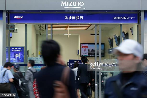 A man center enters a Mizuho Bank Ltd branch while pedestrians walk past the bank in Tokyo Japan on Tuesday May 12 2015 Mizuho Financial Group Inc is...