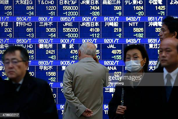 A man center looks at an electronic stock board outside a securities firm in Tokyo Japan on Friday March 14 2014 Japanese shares fell with the Topix...