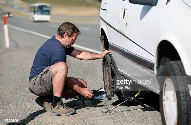 man changes flat tire by the highway - flat tire stock pictures, royalty-free photos & images