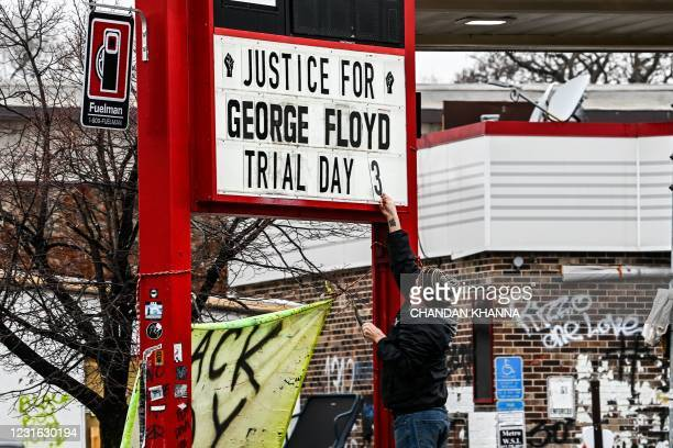 Man changes the number of a sign board at a makeshift memorial of George Floyd before the third day of jury selection begins in the trial of former...