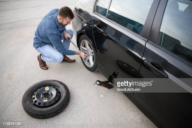 man changing a flat tire - flat tire stock pictures, royalty-free photos & images