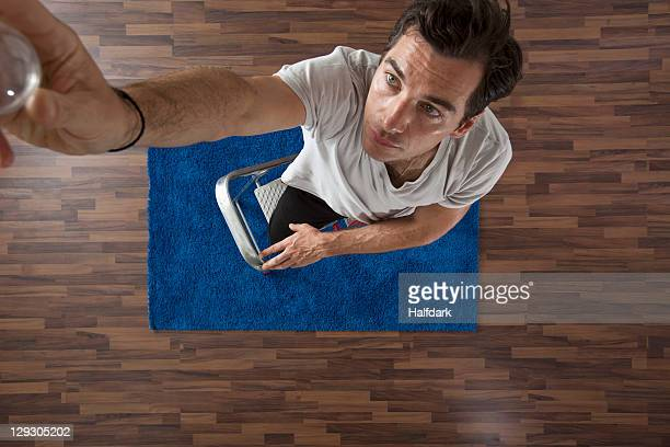 a man changing a light bulb, overhead view - putting stock pictures, royalty-free photos & images