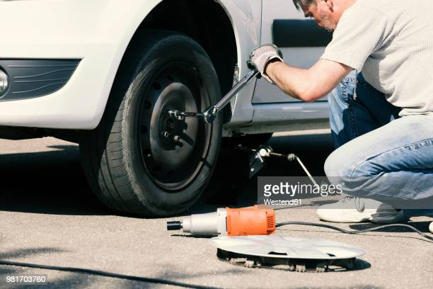 man changing car tire - flat tire stock pictures, royalty-free photos & images