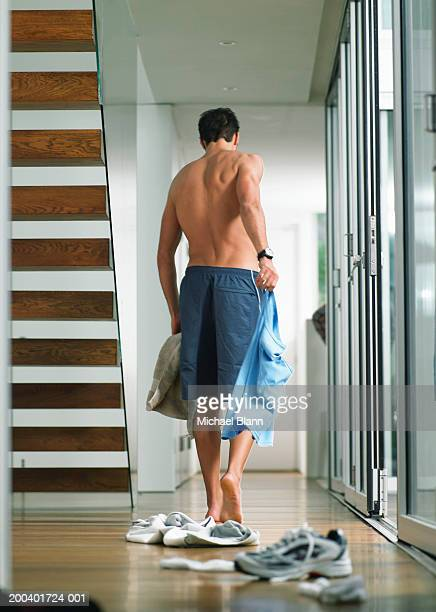 Man changing in hallway, trainers on floor, rear view