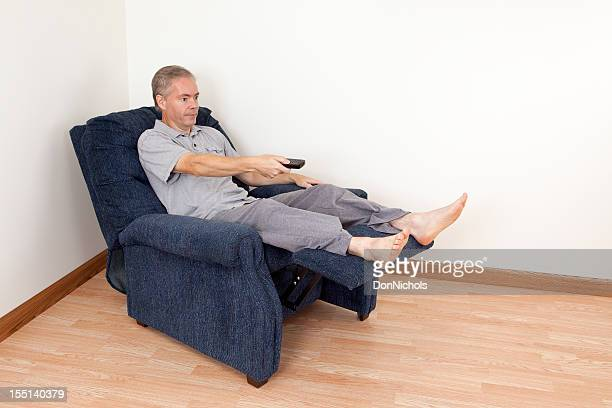 man changing the channel - reclining chair stock photos and pictures