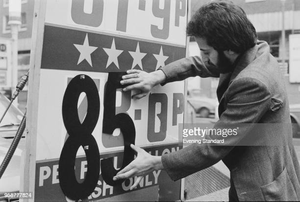A man changing the price on a sign of a petrol station UK 1st February 1978