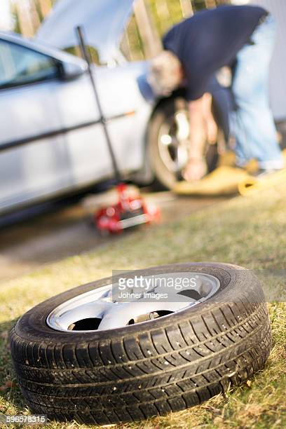 Man changing tire, spare wheel on foreground