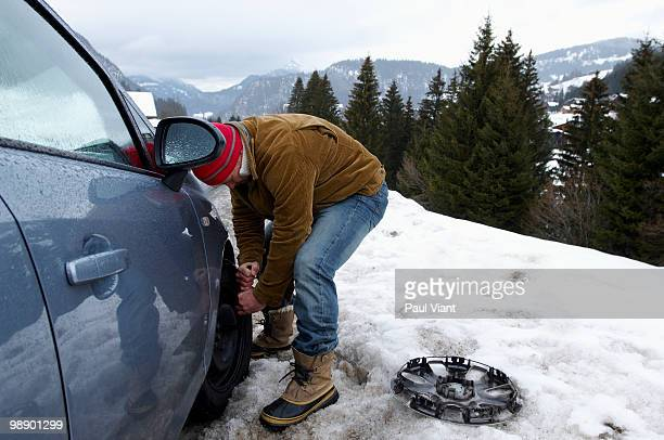 man changing tyre in snow - flat tire stock pictures, royalty-free photos & images