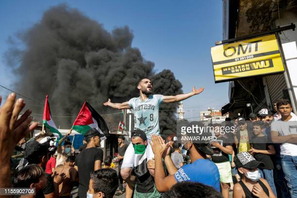 A man chants slogans while lifted on the shoulders of another wearing a Palestinian flag as a bandanna as protesters block the main road outside the...