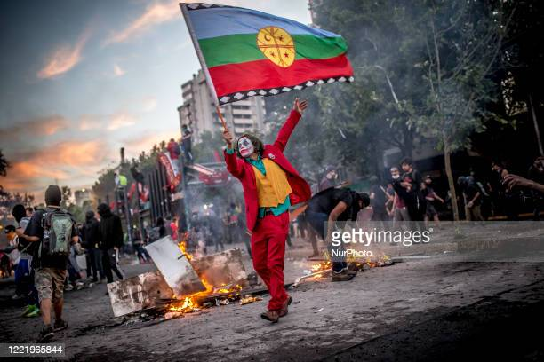 Man characterized by the character 'Joker' waves a flag of the Mapuche people in front of a barricade in the famous' Plaza de la Dignidad ', during...