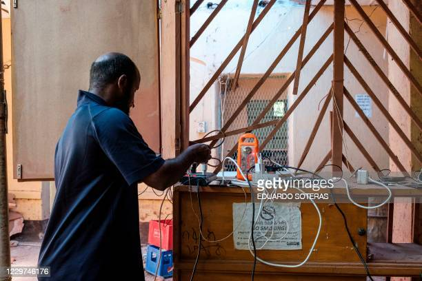 Man charges his phone at a bar in Humera, Ethiopia, on November 22, 2020. - The city has been without electricity from November 9, 2020 and access to...