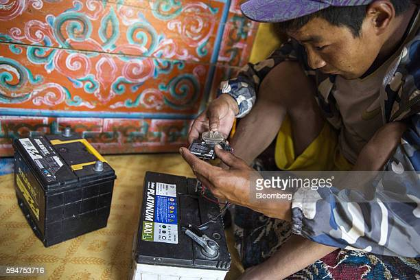 A man charges his phone battery in Ikh Tamir Mongolia on Tuesday Aug 2 2016 Mongolia a mineralrich and landlocked $12 billion economy bordering...