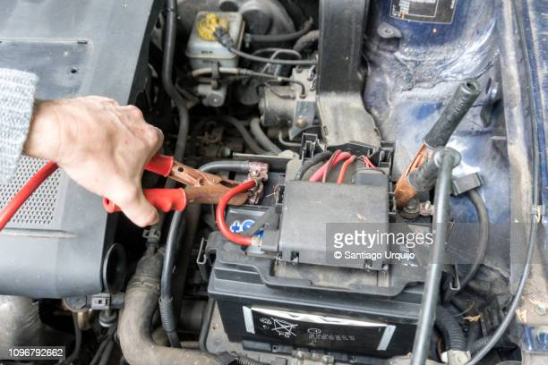 man charging a car battery with a jumper cable - cavo d'acciaio foto e immagini stock