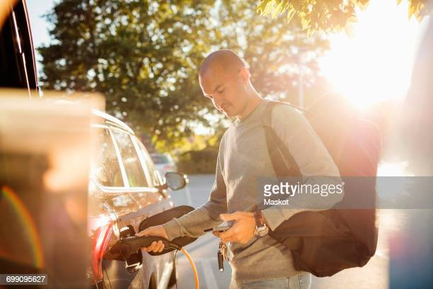 man charging car while using mobile phone at electric station on sunny day - alternative fuel vehicle stock pictures, royalty-free photos & images
