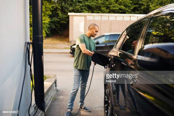 man charging electric car by house - electric car fotografías e imágenes de stock
