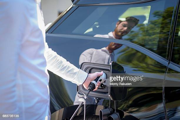 man charging electric car, close up detail - morality stock photos and pictures