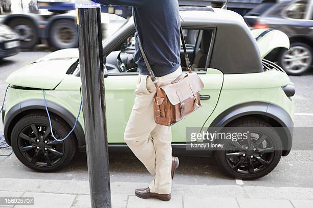 man charging electric car on city street - nancy green stock pictures, royalty-free photos & images