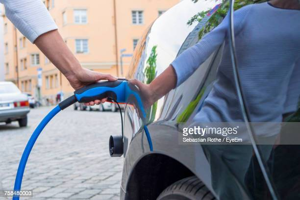 Man Charging Electric Car On Street In City