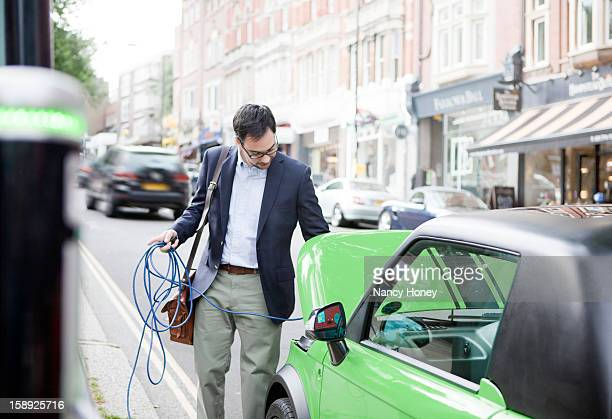 man charging electric car on street - electric car stock pictures, royalty-free photos & images