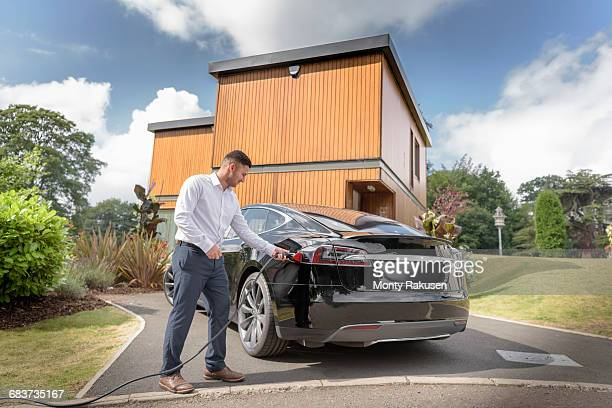 man charging electric car outside modern house - elektroauto stock-fotos und bilder