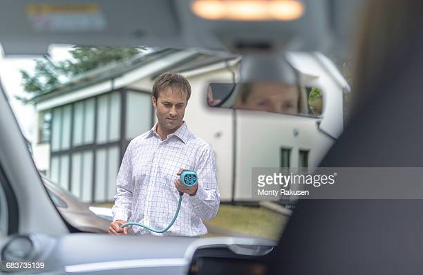 Man charging electric car, seen through car interior
