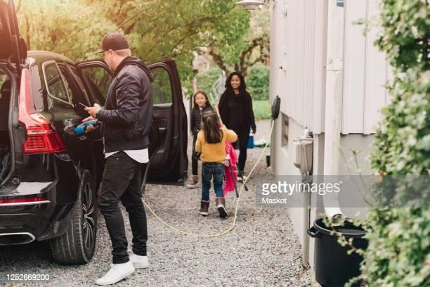 man charging electric car while family loading luggage - beladen stock-fotos und bilder