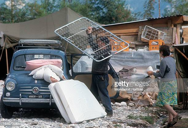 A man charging on the roof of a car the sprung bed base taken from their homes destroyed by the earthquake FriuliVenezia Giulia May 1976