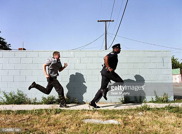 man chasing police officer down sidewalk - chasing stock pictures, royalty-free photos & images