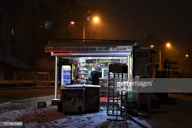 A man chat with the owner of a kiosk during a heavy snowfall in the winter season in Ankara Turkey on December 25 2018